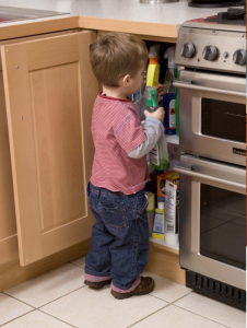 Bērns pie mazgājamo līdzekļu skapja